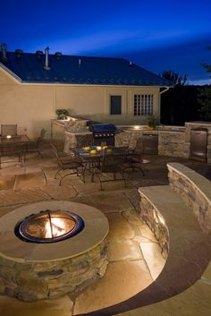 Backyard - covered patio area with large stone fireplace and bbq area with a sink, fridge, and bbq surrounded with stone. Stone bar area with stools, frigde, sink and instead of the fire pit have an large round table surrounded with bench seating in wood (not stone)...