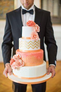 man holding wedding cake, black tux, white and peach cake, pantone blooming dahlia, salmon pink, coral peach