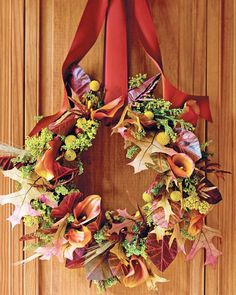 Hung on the door with cranberry red satin ribbon, this stunning #autumn #wreath is an inviting greeting for friends and family. Visit our site to learn how to make this #seasonal door #decor!
