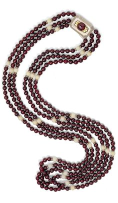 Cartier - An Art Deco garnet and coral necklace, circa 1930. Composed of three rows of garnet beads, interspersed with white coral beads to a silver clasp set with an oval cabochon garnet, signed Cartier, length 78.0cm. #Cartier #ArtDeco #necklace