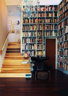 The library and double-height hallway in an architect's house in Los Feliz, California. The bookshelves, probably 14 feet tall, are painted blue (to match the chandelier?) and the taller shelves are accessed by an extra-tall rolling library ladder. Floor To Ceiling Bookshelves, Bookshelves Built In, Bookcases, Bookshelf Wall, Built Ins, Bookcase Stairs, Bookshelf Ideas, Book Stairs, Storage Stairs