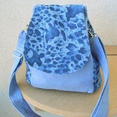 """Kabelko-batůžek """"Modrý leopard"""". Materiál v barvě sv.modrá a """"leopard"""" v různých odstínech. Vypodšívkovaný.  Zapínání na šnůrku a magnetek. Stříbrné komponenty.  Uvnitř jedna kapsa na mobil a poutko s kroužkem na klíče.  Můžete nosit jako kabelku přes rameno a nebo, po malé úpravě, jako batůžek.  Rozměry:dno 22x12 cm, výška 24 cm.  Jediný kus, originál. Dvojí využití jednoho výrobku. Můžete nosit jako kabelku přes rameno a nebo, po malé úpravě, jako batůžek."""