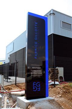 Totem en aluminium laqué brun noir avec lettres PMMA incolore et bleu diffusant en marqueterie, coquille PMMA bleu diffusant, éclairage en aluminium laqué et plaque PMMA incolore - Fabrice Gillotte - Norges-la-Ville