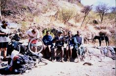 AWOL Tours Director Sally Petersen on cycling trip through Africa - changing a flat tyre with onlookers carrying AK47!