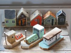 Little Beach Houses with Little Hose Boats. Doesn't get much cooler than that. Very charming idea with lots of color & I do ike the red house in the back with its cheeky little sky light window ;)