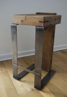 Un taburete de  hierro, con asiento y trasera en tablas de madera reciclada.