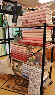 This is perfect.... my dream. A big rolly shelf thingamabob, neat stacks of fabric, and a sewing form.