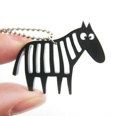 - Details - Sizing - Shipping A necklace featuring a pendant made in the silhouette of a zebra with cut out animal print detail! Check out our collection of zebra themed animal jewelry and products in