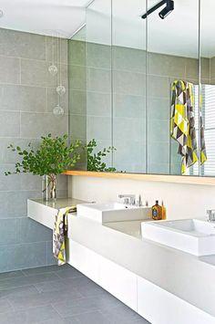 I specchi fino al soffitto e lo spazio aperto sotto i lavandini contribuisce a far sembrare il bagno più grande e spazioso. Le luci a sospensione a forma sferica aggiungono un sottile dettaglio alla stanza