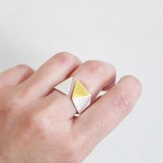 This precious geometric silver ring is handcrafted with fine gold, inspired by 'Polygon' shape.   The ring is made of two precious metals, contrast beautifully with one another. This geometric ring is hand-formed using traditional goldsmith methods from sterling silver, inlaid and forged into silver with rich 24ct gold. The faceted surface makes it reflect beautifully with light. Very minimalist style and comfortable to wear. It's absolutely precious gift for someone special.  ...