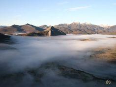 Peña Tremaya arropada por un manto blanco de niebla en el parque natural fuentes carrionas y fuente cobre en la montaña palentina.