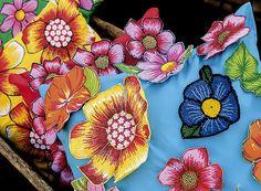 Almofadas: nos tecidos lisos são costuradas as mesmas flores recortadas da estampa de chita e, em algumas, são também feitas flores de crochê, como na azul, em destaque (Foto: Fabio Antonio Ronaldo/ Editora Globo)