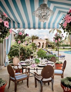 Mario Buatta designed this Palm Beach, Florida, home for preeminent hosts Hilary and Wilbur Ross. Sheltered by an awning made from a Jerry Pair stripe, a poolside dining area features hibiscus standards and chairs cushioned in a Giati Designs fabric.