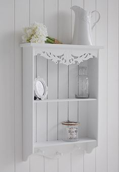 A White Wall Shelf With Pegs For Hanging Perfect For A Nursery White Bathroom