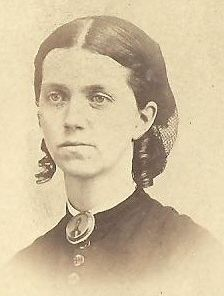 Notice her broach. It is a memorial broach, of a man- could be husband or brother.