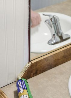 How to create a DIY rustic framed bathroom mirror, the EASY WAY! Follow these simple steps to give your builder grade mirror a makeover! #DIYframedmirror #Woodframedmirror #BudgetBathroomMakeover #BathroomMirror