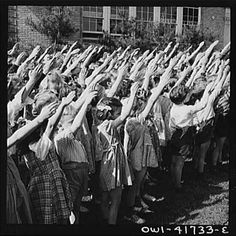 Before 1942, American children pledged allegiance to the flag with the Bellamy Salute so named after Francis Bellamy who wrote the pledge of allegiance in 1892. Worried that it might be confused with the Nazi's Roman salute, Congress changed the salute to simply placing a hand over the heart.