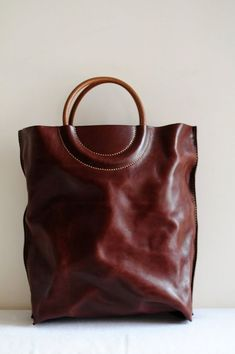 beautiful big dark leather shopper with round handles that are sewn in intriguingly.