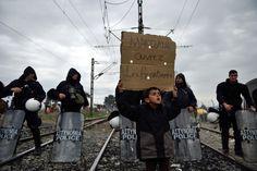 Un enfant migrant tient une pancarte « Macedonia, ouvrez les frontières » lors d'une protestation à Idomeni (Grèce), village-frontière avec la Macédoine, samedi 12 mars 2016.