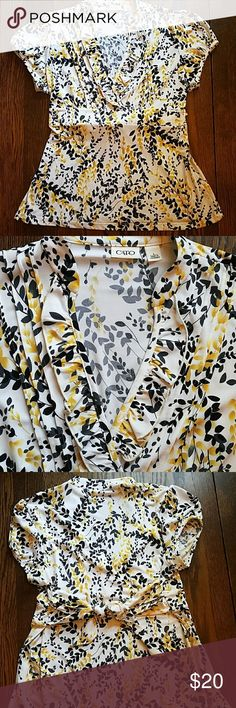 Blouse Short sleeved blouse with black and yellow flower print. Ruffle detailing at neckline and ties in the back to accentuate waist. Cato Tops Blouses