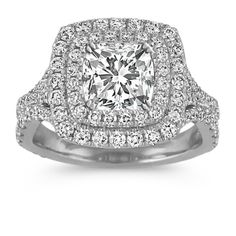 $2995  This double halo engagement ring combines intricate side engraving and milgrain detailing to create this beautiful ring design. One-hundred and sixteen round diamonds, at approximately 1.15 carats total weight, are set in quality 14 karat white gold to create this lovely ring. Simply add the gemstone of your choice at approximately 1.25 carats to complete the look. The ring is 13.5mm wide at the center and 2.5mm at the band.