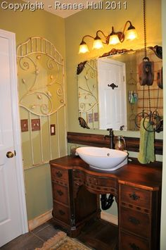 My upstairs bathroom that I recently remodeled with vintage and re-purposed items. I couldn't find tile to match what I already had when we took out the cabinet, so I found an old door and used it to fill the space under the sink counter.  It makes me happy!