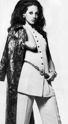 Marisa Berenson - 1968 Metallic gilded greatcoat. Brocade in a pattern of silver end green and gold. With a golden cream crepe sleeveless tunic, a straight pair of trousers. from Tony Armstrong