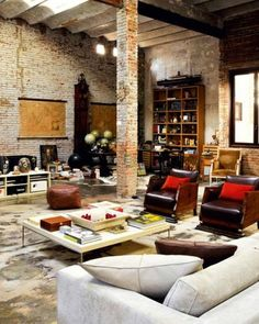 I love the high ceilings, exposed brick, tall shelf in the background, and those great leather chairs.