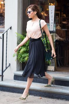Eva Mendes wearing a belted black skirt, pink top and floral heels on the street in NY