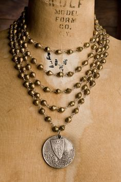 5 strand Joan of Arc necklace by Shannon Koszyk. Handmade Ethiopian bronze beads, sterling wire, chain, Joan of Arc medal, lobster clasp and crosses in back.