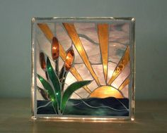 A brilliant stained glass light to enjoy in two different patterns. One side a water lily scene in shades of pink, dark green, light green textured, and a rich turquoise. On the other side a few cattails in green, golden yellow, pale blue and dark blue green. Made of stained glass, #StainedGlassLight