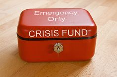 Closed red cash tin marked Crisis Fund - Emergency Only ,Crisis Fund. Closed red cash tin marked Crisis Fund - Emergency Only ,