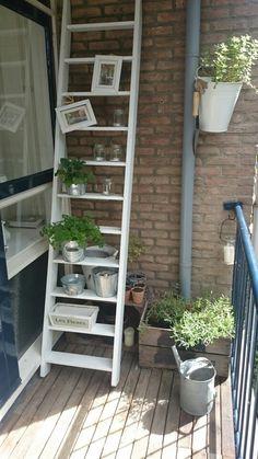 Urban tuinieren. Ladder op balkon met kruidenpotjes en kaarsjes.