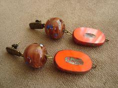 Brinco com pingentes esférico de murano castanho com bolinhas coloridas e oval de murano laranja neon e marrom. Peças em metal na cor ouro velho. R$36,00