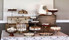 Silver and gold cake plates perched on vintage 1940s steamer trunks and lockers. Dessert table from Jenny Cookies.