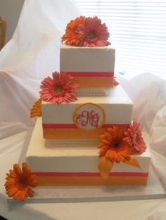 Square cake with pink and orange flowers.
