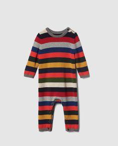 Pelele en tricot con estampado de rayas multicolor, de manga larga y cuello redondo. Tiene el cierre en el hombro y en la entrepierna mediante botones.
