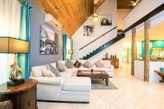 Open plan living area at Hummingbird House, Roatan. Black, white & grey color palette with turquoise silk curtains & accent wall.