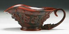 """A Chinese Antique Carved Rhinoceros Horn Libation Cup: finely carved as a libation cup with Chi dragon shaped handle, the horn ranging from deep brown to caramel tone, probably of early Qing Dynasty  Dimensions: L: 7"""""""