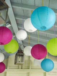 Paper lanterns in a rainbow of hues resemble a bundle of balloons when strung by ribbons from a porch ceiling.