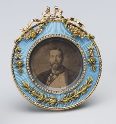 Fabergé frame in three-colour gold, light blue guilloché enamel, half pearls, and ivory, 1908, with a photograph of King George V. Acquired by Queen Mary, consort of George V.