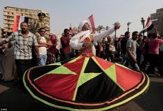 An Egyptian Tanoura folk dancer dances around crowds in Tahrir Square in Cairo. On the same day at least 51 people were killed