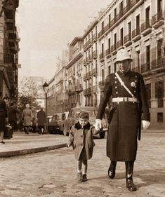 1960. Un guardia urbano, ayudando a cruzar la calle a una niña, en el cruce de las calles de Ayala con Serrano. 1960