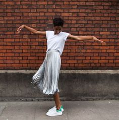 White t-shirt, silver pleated skirt, and white sneakers