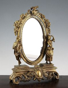 <b>A late 19th century French oval ormolu dressing table mirror,</b> decorated with figures, floral bouquets and scrolling acanthus decoration, <i>13in.</i>