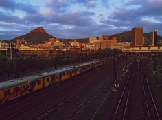 And the sun started to shed its morning warmth on the beautiful city as the train was leaving into the unknown.... Oh the beauty we have to endure every day.  #landscape #mood #trains #mountain #cityscape #railway #mobilephotography #clouds #sunrise #shotoniphone #colours #morning #photo #beauty #photography #landscapephotography