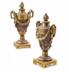<b>PAIR OF GEORGE III GILT BRONZE AND FELDSPAR CASSOLETTES IN THE MANNER OF MATTHEW BOULTON</b> <br /> 18TH CENTURY <br /> each with a flaming finial cover and two handles hung with swags, on a turned and fluted spreading column and square plinth base (2) <br /> 19cm high