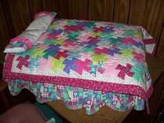 Doll bed and quilt.  The base of the bed is a plastic storage container.