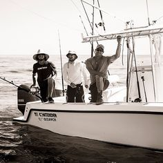 First Mate Todd Goggins, Deck Hand Whitey, and Fishing Master Brett McBride work to deliver the Tiger Sharks to the Australian scientists during the expedition.