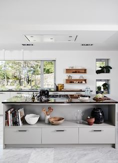 Minimal Scandinavian kitchen in grey. Real Stone Worktops and gorgeous green view.